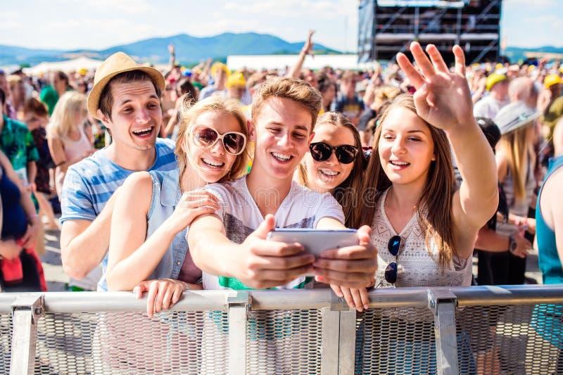 夏天音乐节的少年在采取selfie的人群 免版税库存图片