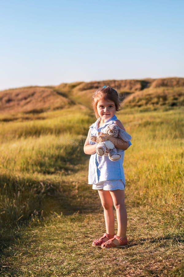 夏天领域的愉快的女孩在日落 库存照片