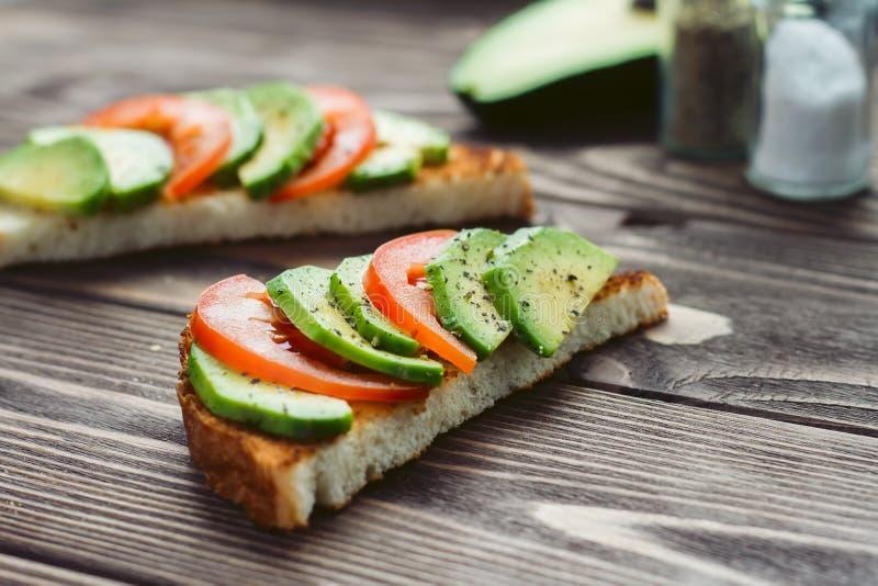 夏天颜色三明治用红色蕃茄和在一张木桌上的绿色鳄梨片 库存图片