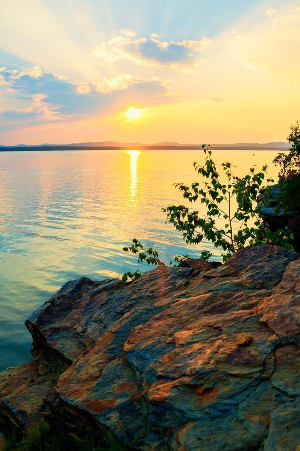 夏天风景-在发光和湖的点燃的边缘的夏天树石峭壁日落光 免版税库存图片