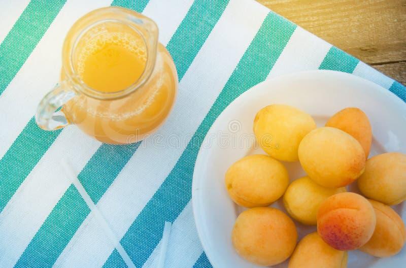 夏天饮料和果子新鲜的杏子汁在一个玻璃水罐和成熟杏子在餐巾,顶视图,室外 库存图片