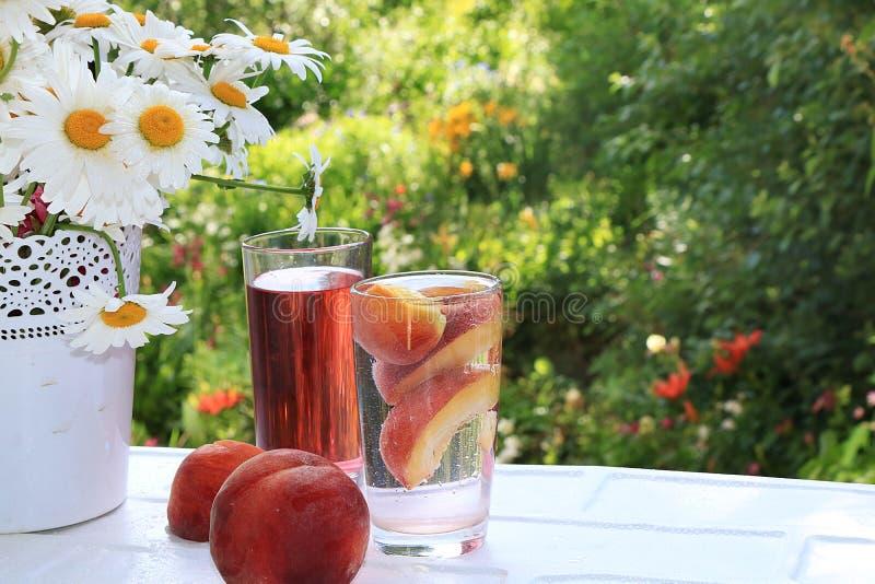 夏天饮料用果子在湿开窗口里对庭院 刷新的梨和桃子柠檬水用果子和一个花瓶与 免版税库存图片