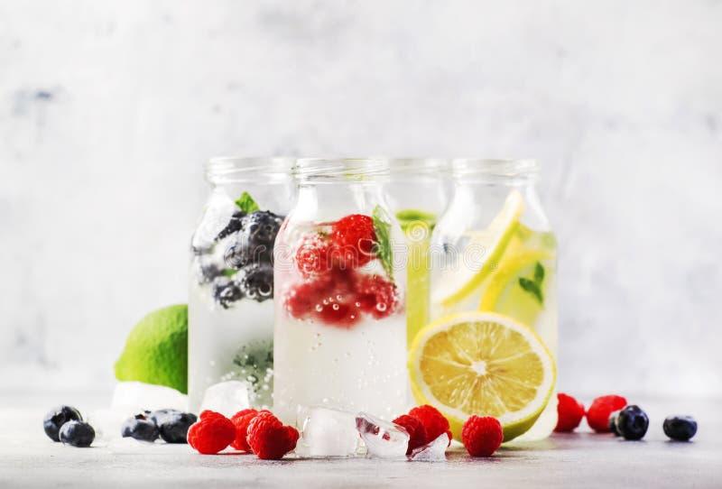 夏天饮料集合 莓果、果子和柑橘非酒精刷新的冰冷的饮料和鸡尾酒在玻璃瓶在白色 图库摄影