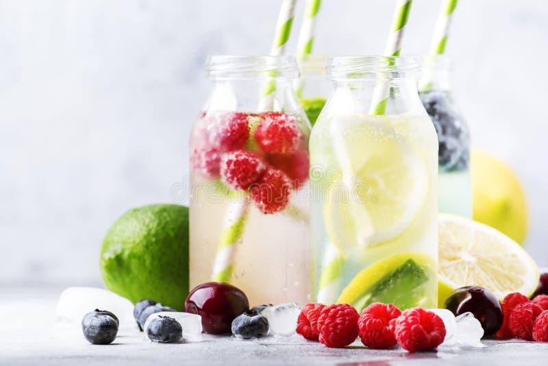夏天饮料集合 莓果、果子和柑橘非酒精刷新的冰冷的饮料和鸡尾酒在玻璃瓶在白色 库存图片