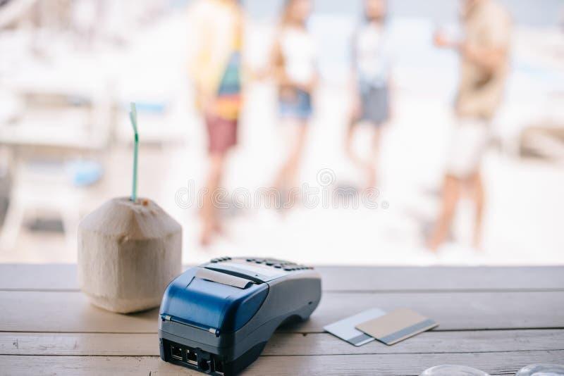 夏天鸡尾酒特写镜头视图与吸管和付款终端的有在酒吧柜台的信用卡的 免版税库存照片