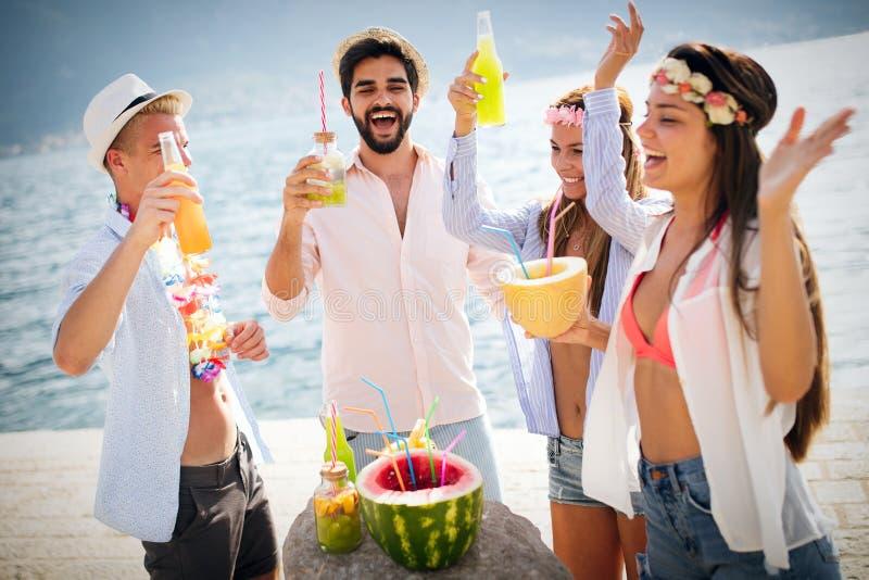 夏天,假期,党,人概念 有小组的朋友乐趣和党在海滩 免版税库存图片