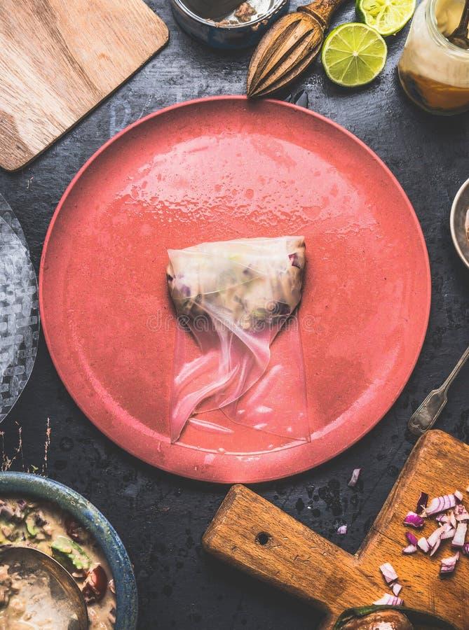 夏天滚动与罐装金枪鱼装填,逐步做在与板材、通行费和成份的土气厨房用桌 图库摄影