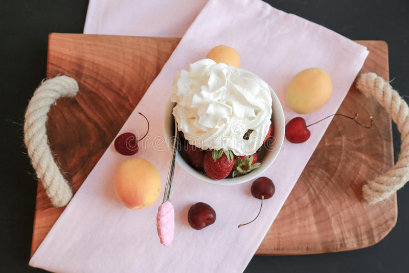 夏天结果实-与奶油的草莓点心对此和桃子和樱桃在木桌上 免版税库存图片