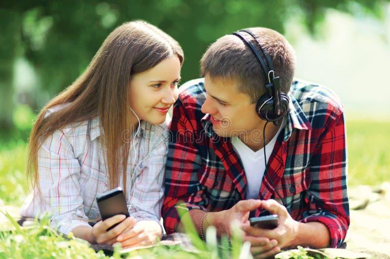 夏天画象年轻夫妇说谎的放松在草听到在耳机的音乐在智能手机 库存照片
