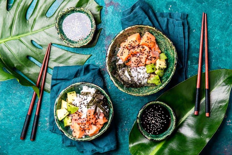 夏威夷三文鱼poce用鲕梨、米和sesamo在热带叶子的碗服务 绿松石板岩背景 顶层 免版税库存图片