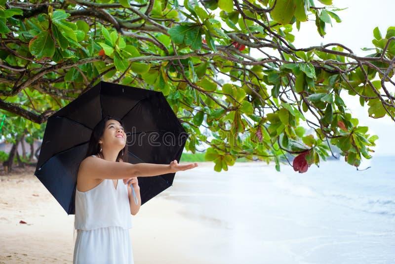 夏威夷海滩的少妇在雨中的拿着伞 免版税库存照片