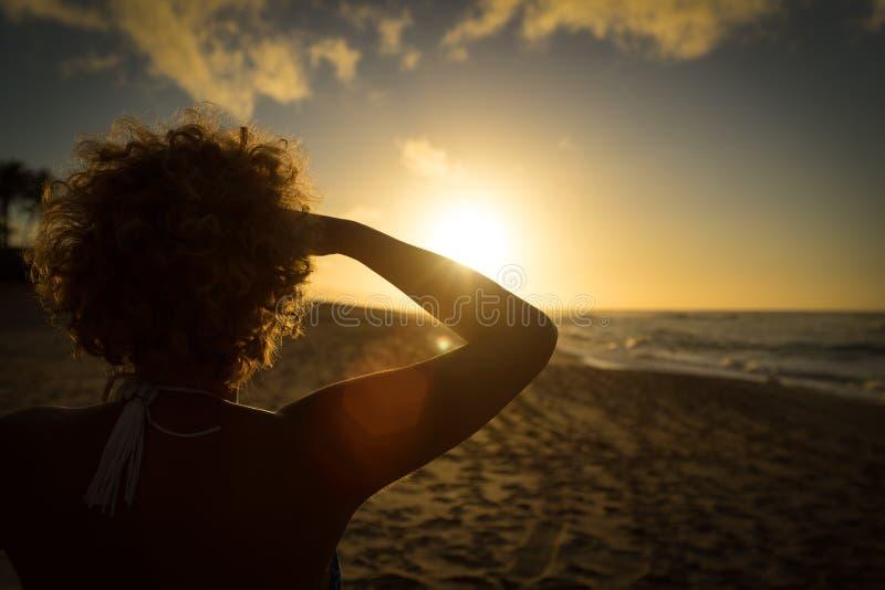 夏威夷海滩的可爱的妇女观看太阳集合的 免版税图库摄影