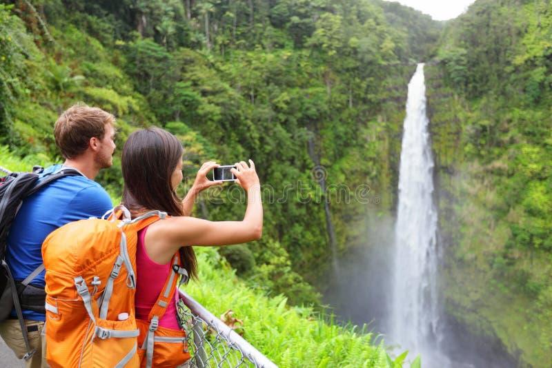 夏威夷的夫妇游人由瀑布 库存照片