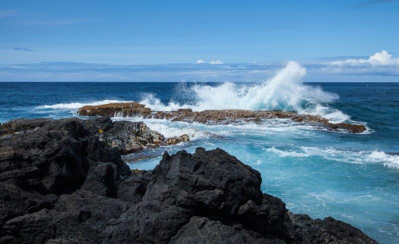 夏威夷的熔岩与大海浪飞溅的岩石海岸 免版税图库摄影