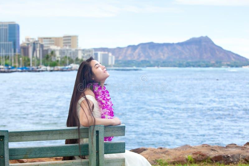 夏威夷青少年与坐由海洋,威基基的列伊在背景中 免版税库存照片