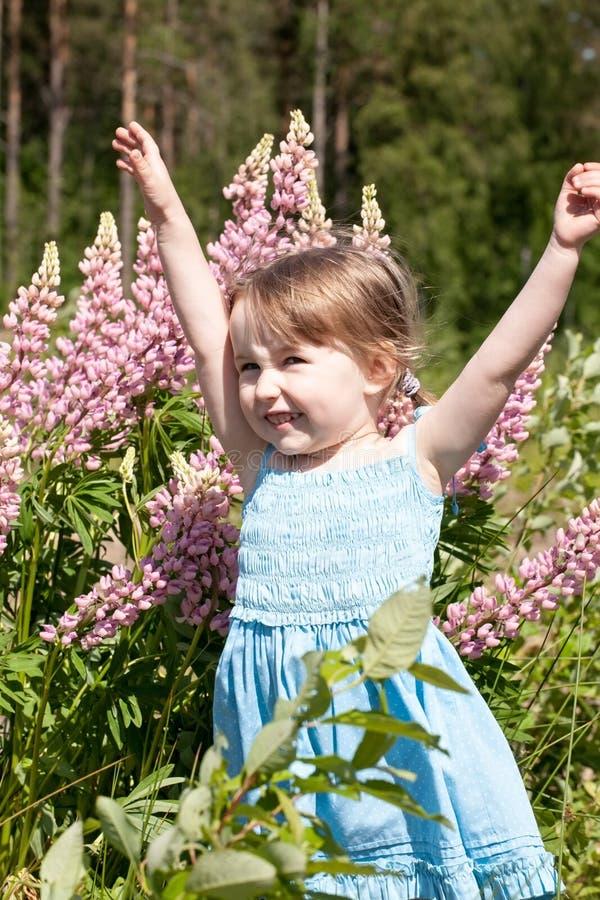 夏日户外背景中,快乐的小女孩双手站着 免版税库存图片