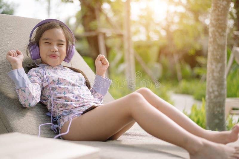 夏日生活方式年轻人亚裔女孩放松听到在游泳场的音乐在海滩胜地户外旅馆 ?? 库存图片