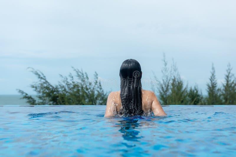 夏时和假期 妇女生活方式松弛和愉快在豪华游泳场sunbath,在海滩胜地的夏日t的 免版税图库摄影