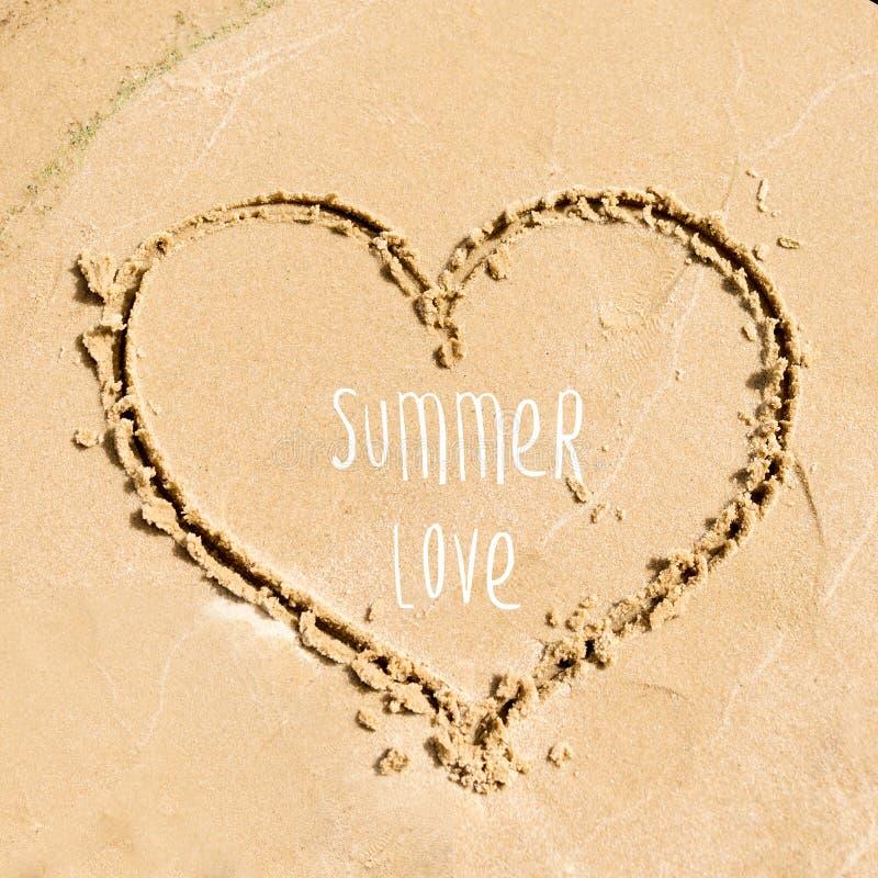 夏时贺卡设计 在海滩的沙子画的心脏的形状 免版税库存照片