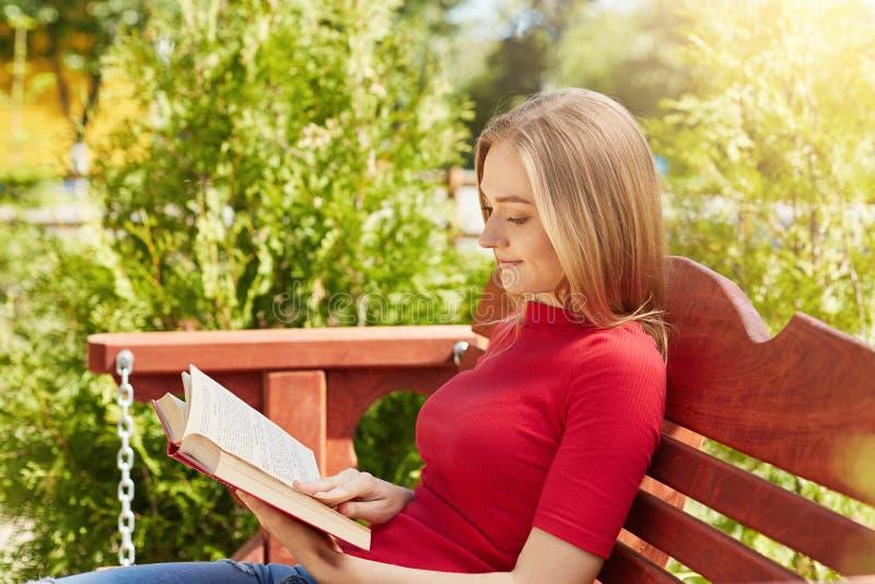 夏令时和休闲概念 穿红色毛线衣的可爱的女小学生斜向一边的画象读殷勤地书准备 免版税图库摄影