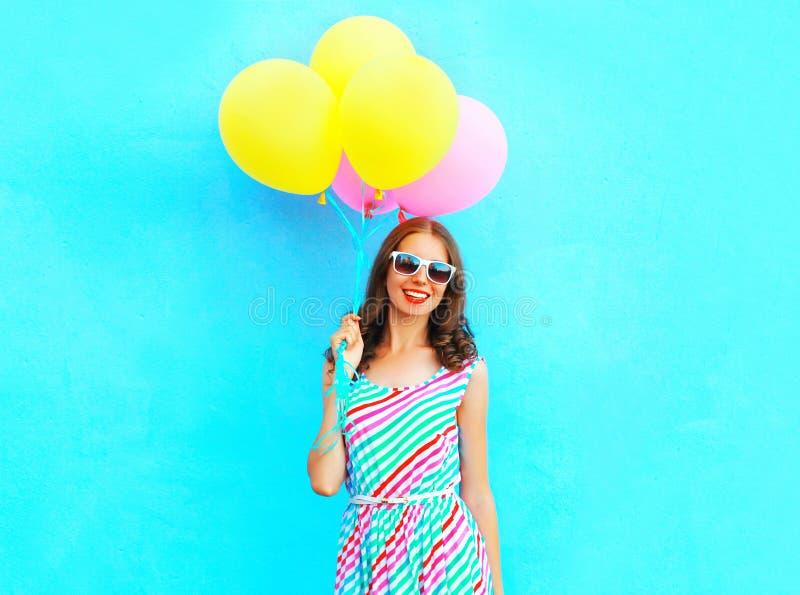 夏令时!愉快的微笑的妇女在手中拿着空气五颜六色的气球 库存图片