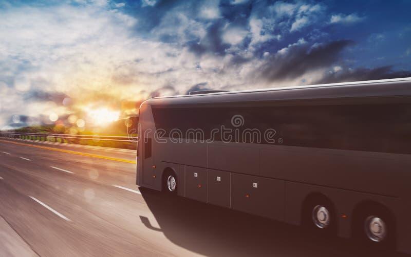 夕阳时,大型旅游巴士在高速公路上快速行驶 库存图片