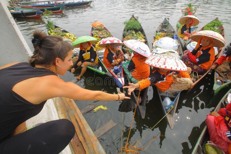 外国游客在印尼班加马辛的浮动市场购物 库存图片