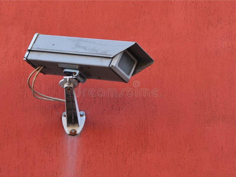外在监督灰色街道照相机在赤土陶器色的修造的墙壁上的 免版税库存图片