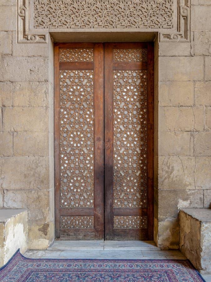 外在老蔓藤花纹装饰了导致Al Rifai清真寺,开罗,埃及的木门 免版税库存照片