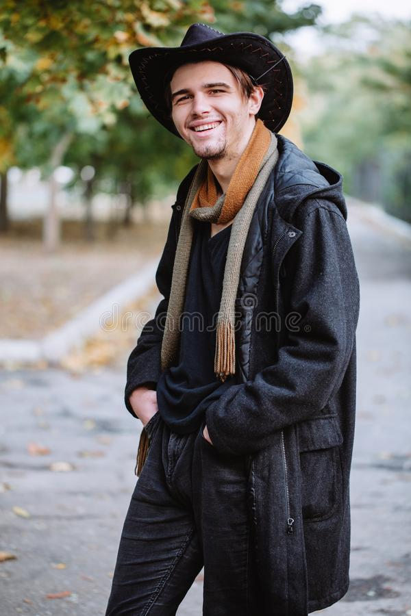 外套和帽子的一个年轻人在公园站立并且微笑 库存图片