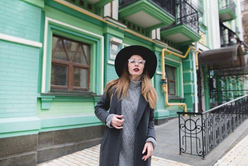 外套和帽子的美丽的时髦的女孩摆在以老镇的建筑学为背景 库存照片