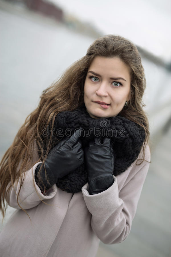 外套和手套的,位可爱的妇女她的嘴唇 一件黑外套、一条围巾和一件红色礼服的女孩反对灰色天空 没查出 库存照片