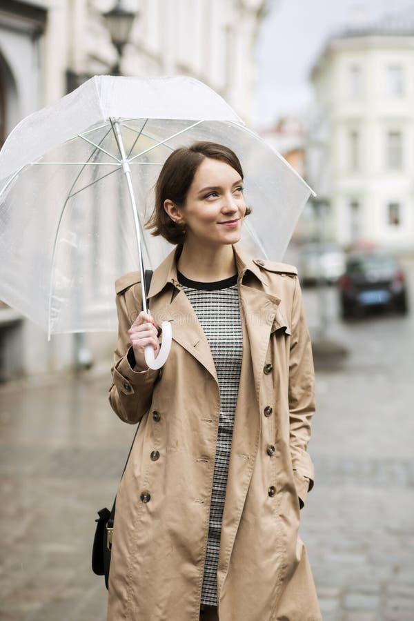 外套的妇女在雨以后的湿街道上 免版税库存图片