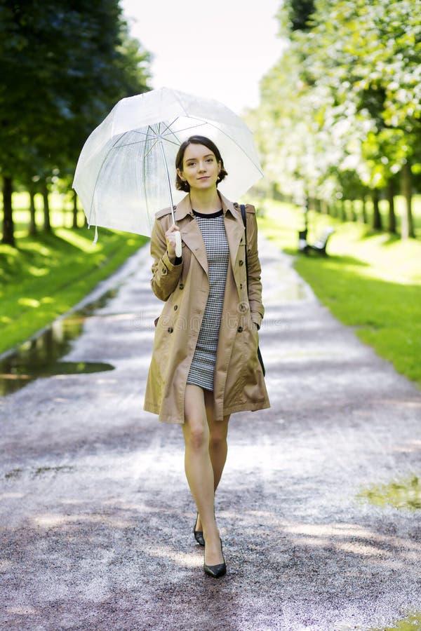 外套的妇女有伞的晴天 免版税图库摄影