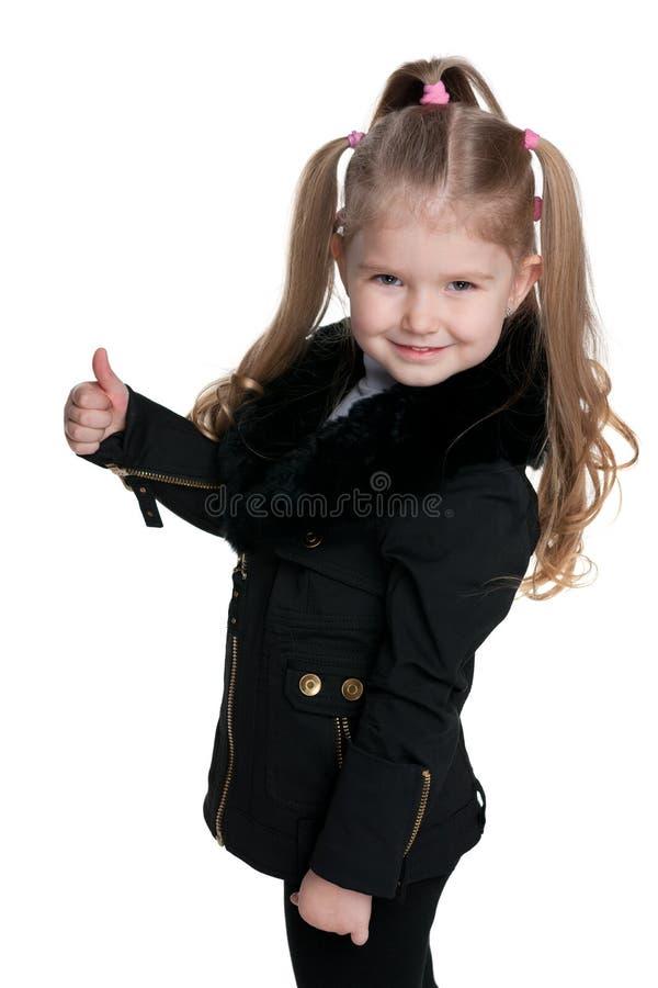 黑外套的小女孩举行她的赞许 免版税库存图片