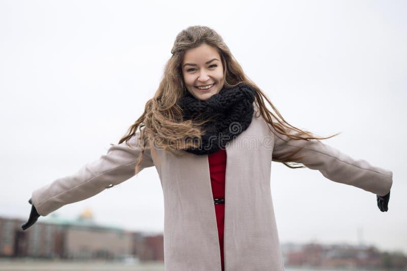 外套的微笑的女孩涂了他的胳膊 一件黑外套、一条围巾和一件红色礼服的女孩反对灰色天空 没查出 免版税图库摄影