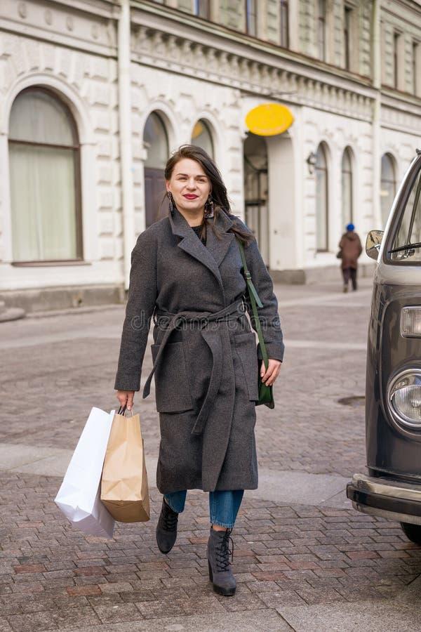 外套的美丽的愉快的妇女步行沿着向下有包裹的街道的 免版税库存图片