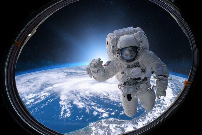 外层空间的宇航员从在地球的背景的舷窗 免版税库存照片