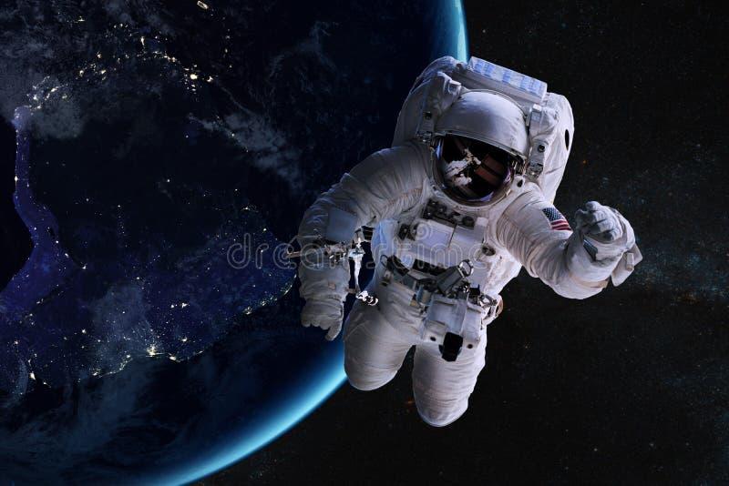 外层空间的宇航员在夜地球的背景 库存图片