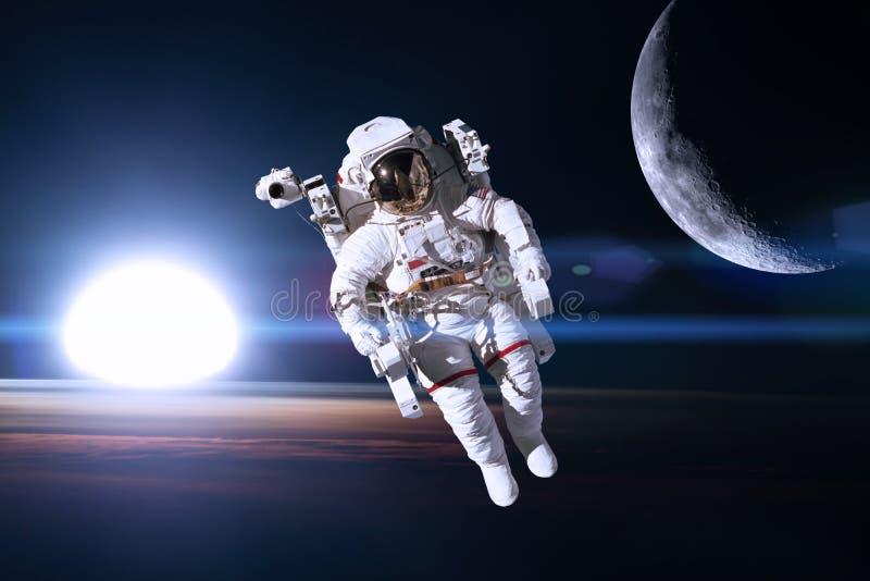 外层空间的宇航员在夜地球的背景 免版税库存图片