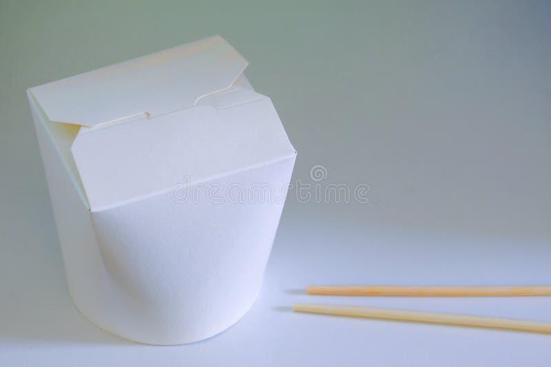 外带亚洲的烹调或交付 韩国,日本或者中国面条或米在一个纸板箱和筷子在白色后面 库存照片