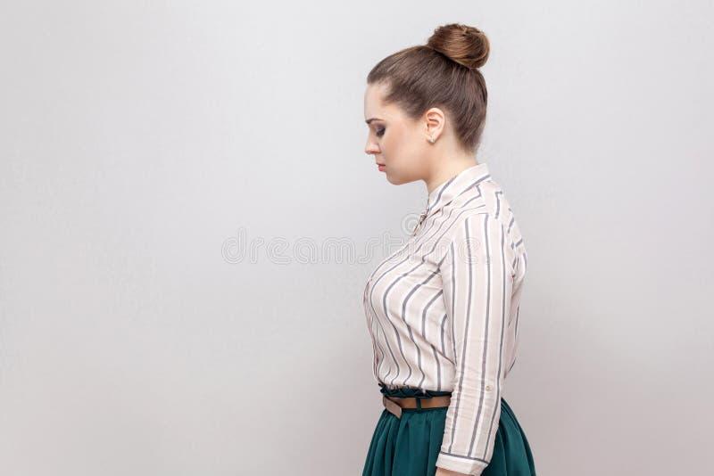 外形不快乐的美丽的年轻女人和收集的禁令发型,身分侧视图画象镶边衬衣和绿色裙子的 免版税库存图片