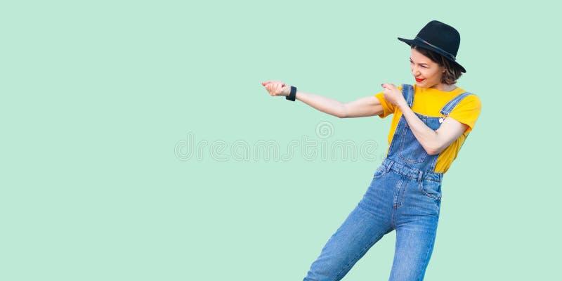 外形俏丽的年轻行家女孩侧视图画象蓝色牛仔布总体、黄色衬衣和黑帽会议身分的与拳头或 免版税图库摄影
