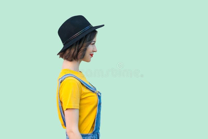 外形俏丽的年轻行家女孩侧视图画象蓝色牛仔布总体、黄色衬衣和黑帽会议身分的,微笑和 库存照片