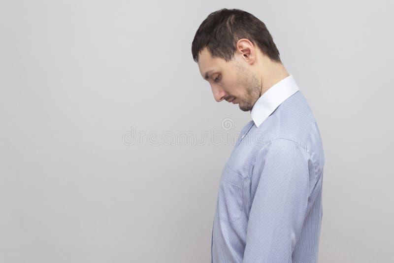 外形哀伤的沮丧的英俊的刺毛商人侧视图画象在经典蓝色衬衣身分藏品头的下来和 免版税图库摄影