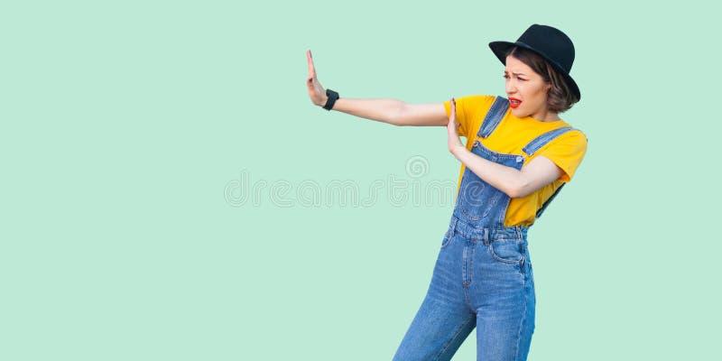 外形害怕的年轻行家女孩侧视图画象蓝色牛仔布总体、黄色衬衣和黑帽会议身分的用中止手 免版税库存图片