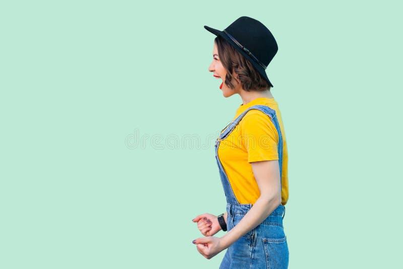 外形惊奇的俏丽的年轻行家女孩侧视图画象蓝色牛仔布总体、黄色衬衣和黑帽会议身分的和 免版税库存照片