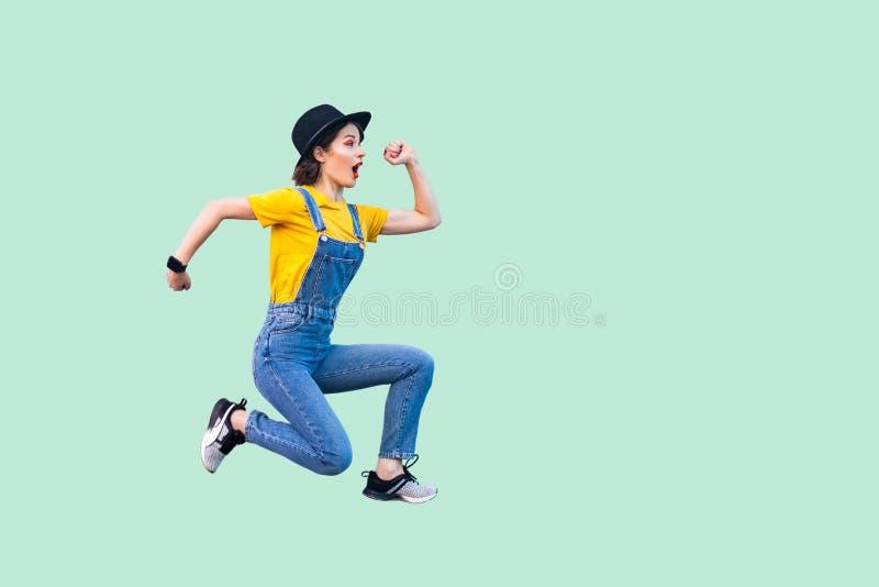 外形惊奇的滑稽的年轻行家女孩侧视图画象蓝色牛仔布总体、黄色跳跃衬衣和的黑帽会议的  库存照片