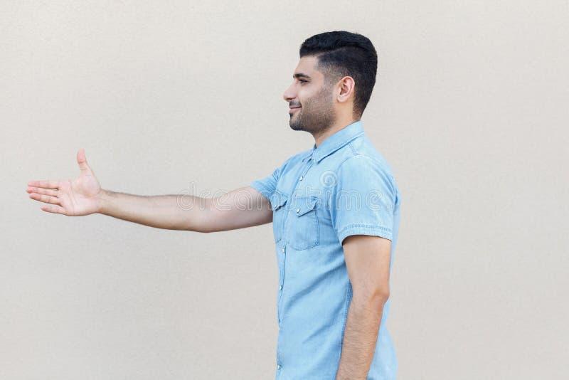 外形愉快的英俊的年轻有胡子的人侧视图画象蓝色衬衣身分和给的手ro问候或成交与 免版税库存照片