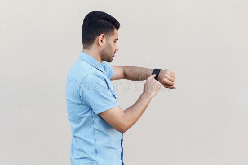外形殷勤英俊的年轻有胡子的人侧视图画象蓝色衬衣身分和使用的他巧妙的手表,接触在 库存照片